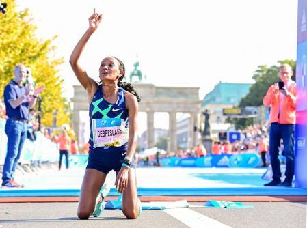 Goytom Gebreslase celebrates winning the women's event, in front of the Brandenburg Gate